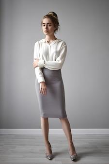 Verticale foto van prachtige stijlvolle jonge europese dame in elegante witte blouse en kokerrok hand op arm, camera staren met een serieuze zelfverzekerde blik. stijl, schoonheid, glamour en mode