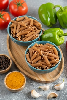 Verticale foto van rauwe penne pasta in kommen met verse biologische groenten.