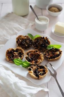 Verticale foto van snacks met champignons, kaas, olijven en basilicum
