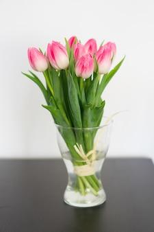 Verticale foto van tulpen in een vaas op tafel onder de lichten