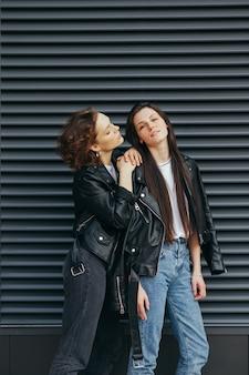 Verticale foto van twee vriendinnen in lederen jassen poseren