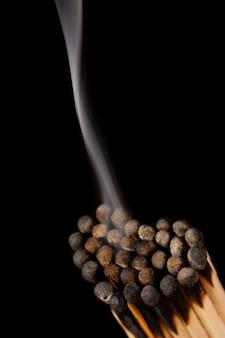 Verticale foto van verbrande lucifers gemaakt in de vorm van een hart tegen zwarte rook afkomstig van lucifers