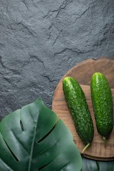 Verticale foto van verse biologische komkommers op een houten bord op zwarte achtergrond.