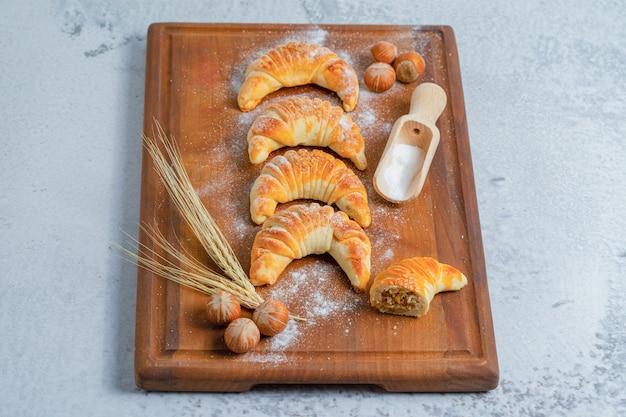 Verticale foto van verse zelfgemaakte croissants op een houten bord over grijs oppervlak.