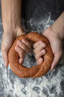 Verticale foto van vrouwenhanden die verse turkse simit houden.