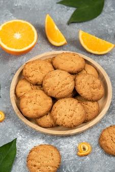 Verticale foto van zelfgemaakte koekjes op een houten bord met stukjes sinaasappel en bladeren over grijs oppervlak.