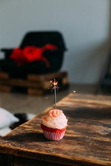 Verticale foto voor smartphone-screensaver van rood fluweelroze cupcake, met sterretjeskaars, versierd met glazuur en suiker
