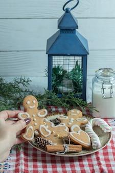 Verticale foto. vrouwelijke hand die koekje van plaat neemt.