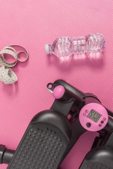 Verticale fotografie, objecten van het fitnessleven, stepper-machine om calorieën te verbranden, meetlint en waterfles op een roze achtergrondvloer.