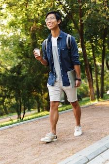 Verticale glimlachende aziatische mannelijke student die in oogglazen met laptop in park loopt