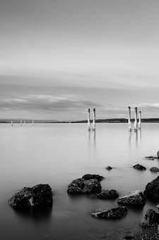 Verticale grijstinten shot van een houten pier in de buurt van rotsformaties onder de bewolkte hemel