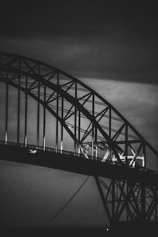 Verticale grijswaarden shot van een moderne ijzeren boogvormige brug