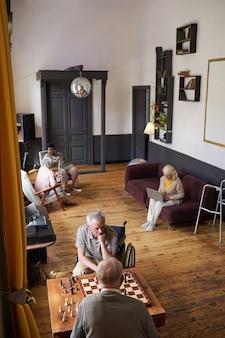 Verticale groothoekopname van senioren die genieten van activiteiten in de kopieerruimte van verpleeghuizen