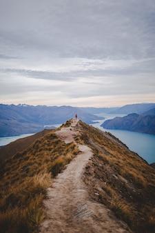 Verticale hoge hoek die van een persoon is ontsproten die zich aan het eind van het lopen van weg op roys peak in nieuw zeeland bevindt