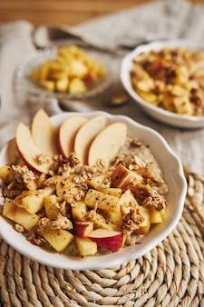 Verticale hoge hoek opname van een kom pap met granen en noten, en plakjes appel op een tafel