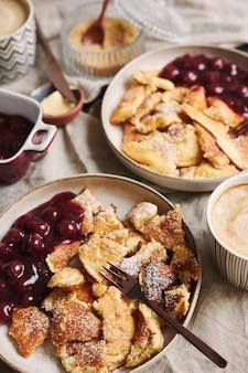 Verticale hoge hoek opname van heerlijke donzige pannenkoeken met kersen en poedersuiker