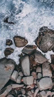 Verticale hoge hoek schot van grote stenen in het stormachtige oceaanwater