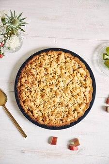Verticale hoge hoek shot van een plaat van knapperige rhabarbar taart taart en enkele ingrediënten op een tafel