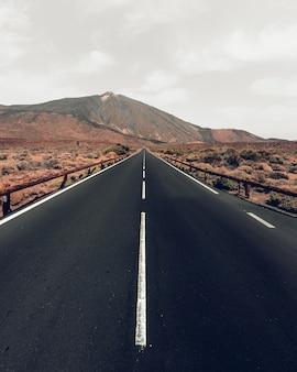 Verticale hoge hoek shot van een snelweg omgeven door heuvels onder de grijze lucht