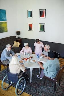 Verticale hoge hoekmening bij diverse groep senioren die genieten van ontbijt aan eettafel in nu...