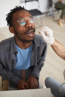 Verticale hoge hoekmening bij jonge afro-amerikaanse man die covid-test doet in vaccinatiecentrum of kliniek
