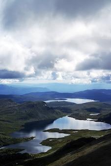 Verticale hoge hoekmening van een landschap met een rivier in de heuvels in tuddal gaustatoppen, noorwegen