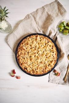 Verticale hoge hoekopname van een bord knapperige rhabarbar-taarttaart en enkele ingrediënten op een tafel