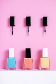 Verticale hoge hoekopname van kleurrijke nagellakken op een roze papier