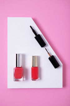 Verticale hoge hoekopname van roze nagellakken op veelkleurig papier