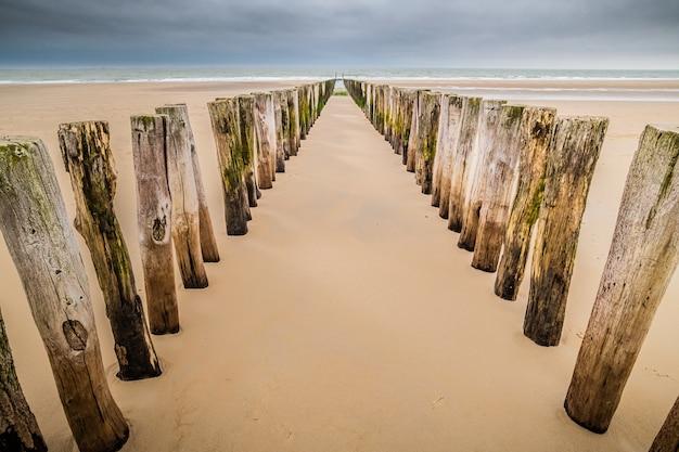 Verticale houten planken in het zand van een onafgewerkte houten dok op het strand onder een bewolkte hemel