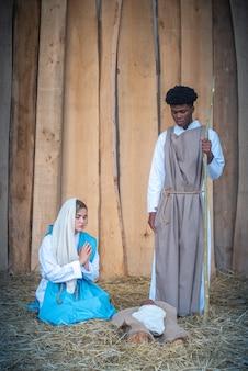 Verticale kerststal met multi-etnische personages in een wieg