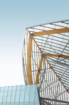 Verticale lage hoek shot van een metalen en houten gebouw onder de blauwe hemel