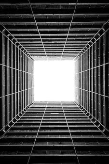 Verticale lage hoekopname in grijstinten van het licht dat door het plafond van een hoog gebouw valt