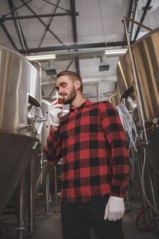 Verticale lage hoekopname van een brouwer die vers gebrouwen bier ruikt, werkzaam in zijn bierfabriek