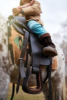Verticale lage hoekopname van een onherkenbaar klein kind dat op een kleine appaloosa-pony zit