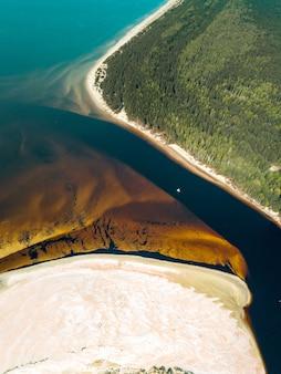 Verticale luchtfoto van een speedboot die langs de rivier vaart aan de kust van goudkleurig zand