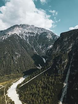 Verticale luchtfoto van groene bergen met witte wolken aan de oppervlakte