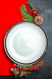 Verticale mening van dinerborden en dennentakken met de conifeerkegel van de decoratie toebehoren op een rood servet