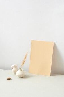 Verticale moderne compositie van handgemaakte keramische vazen verschillende vormen met natuurlijk droog planttakje en verticaal vel papier tegen lichtgrijze achtergrond, kopieerruimte. natuurlijk eco-concept.