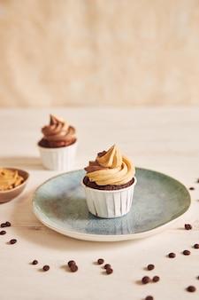 Verticale ondiepe focus close-up shot van heerlijke pindakaas cupcake met romige suikerglazuur op plaat
