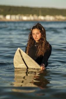 Verticale ondiepe focus van een jonge europese surfer in het water