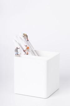 Verticale opname van beeldjes van studenten die op pennen in een pot klimmen