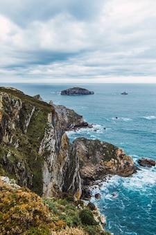 Verticale opname van de bergen in de buurt van de zee onder een bewolkte hemel in cabo penas, asturias, spanje