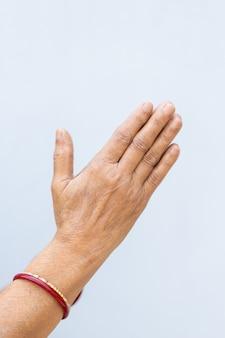 Verticale opname van de biddende handen van een persoon op een grijze achtergrond