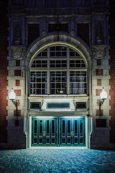 Verticale opname van de gevel van een oud gotisch bakstenen gebouw met verlichte lampen, 's nachts