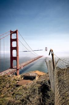 Verticale opname van de golden gate bridge tegen een mistige blauwe lucht in san francisco, californië, vs