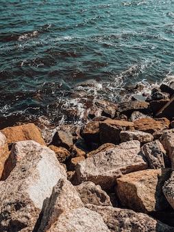 Verticale opname van de golven die de rotsachtige kust bereiken