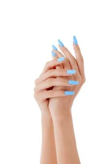 Verticale opname van de handen van een vrouw met blauwe nagellak op een wit oppervlak