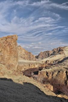 Verticale opname van de prachtige wolken boven de rocky ravine