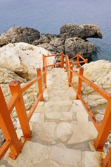 Verticale opname van de trap met een houten hek omgeven door rotsen en stenen in de buurt van de oceaan